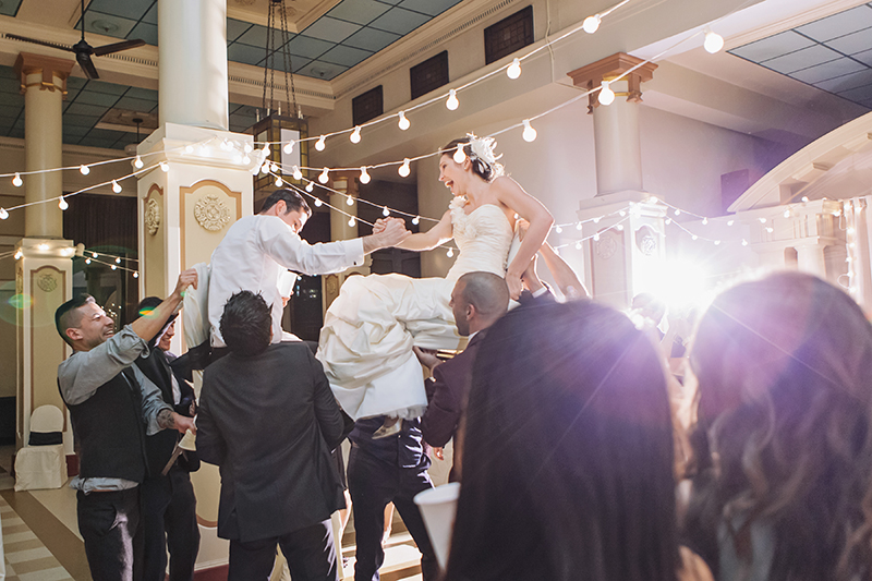 bride and groom raised high on chairs