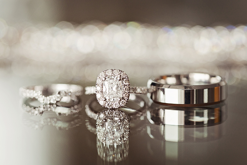 wedding bands and engagement ring with reflection