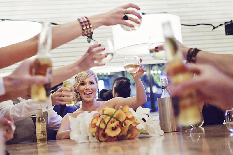 bride cheersing with wedding party