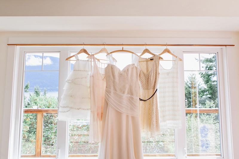 bride and bridesmaids dresses hanging in window