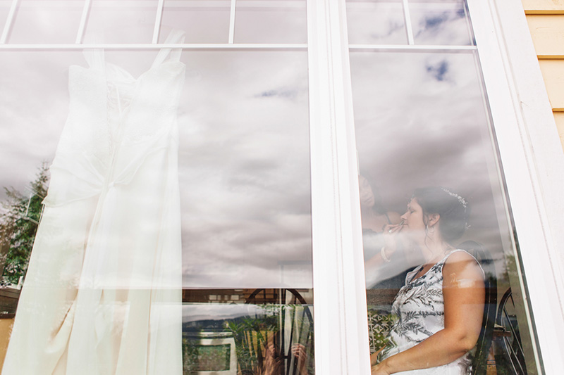 bride having make up done, looking through window