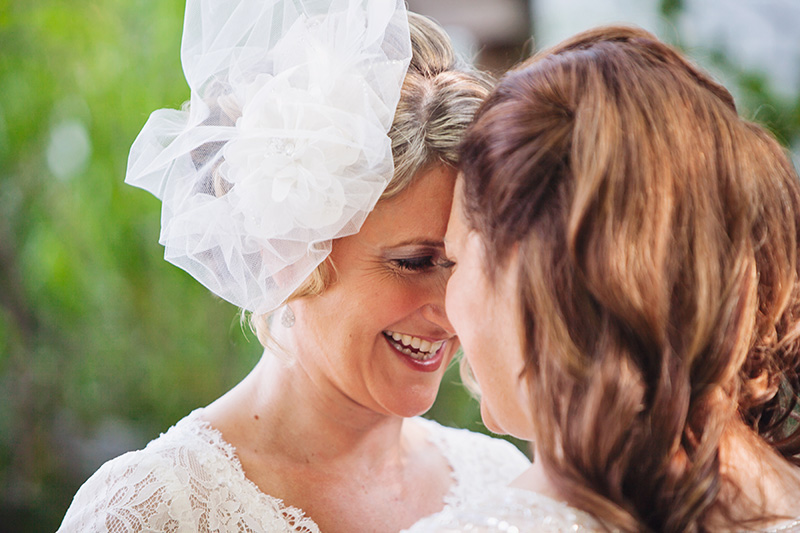 two brides laughing with heads together