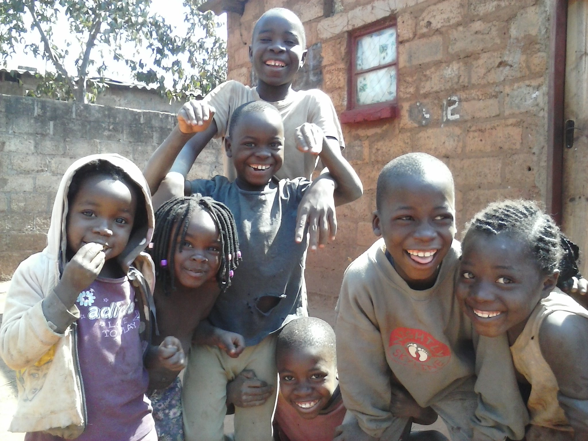 Children from the slum compound of Chainda within Lusaka, Zambia happily pose for a photo taken by Mulenga during a visit in August 2014.