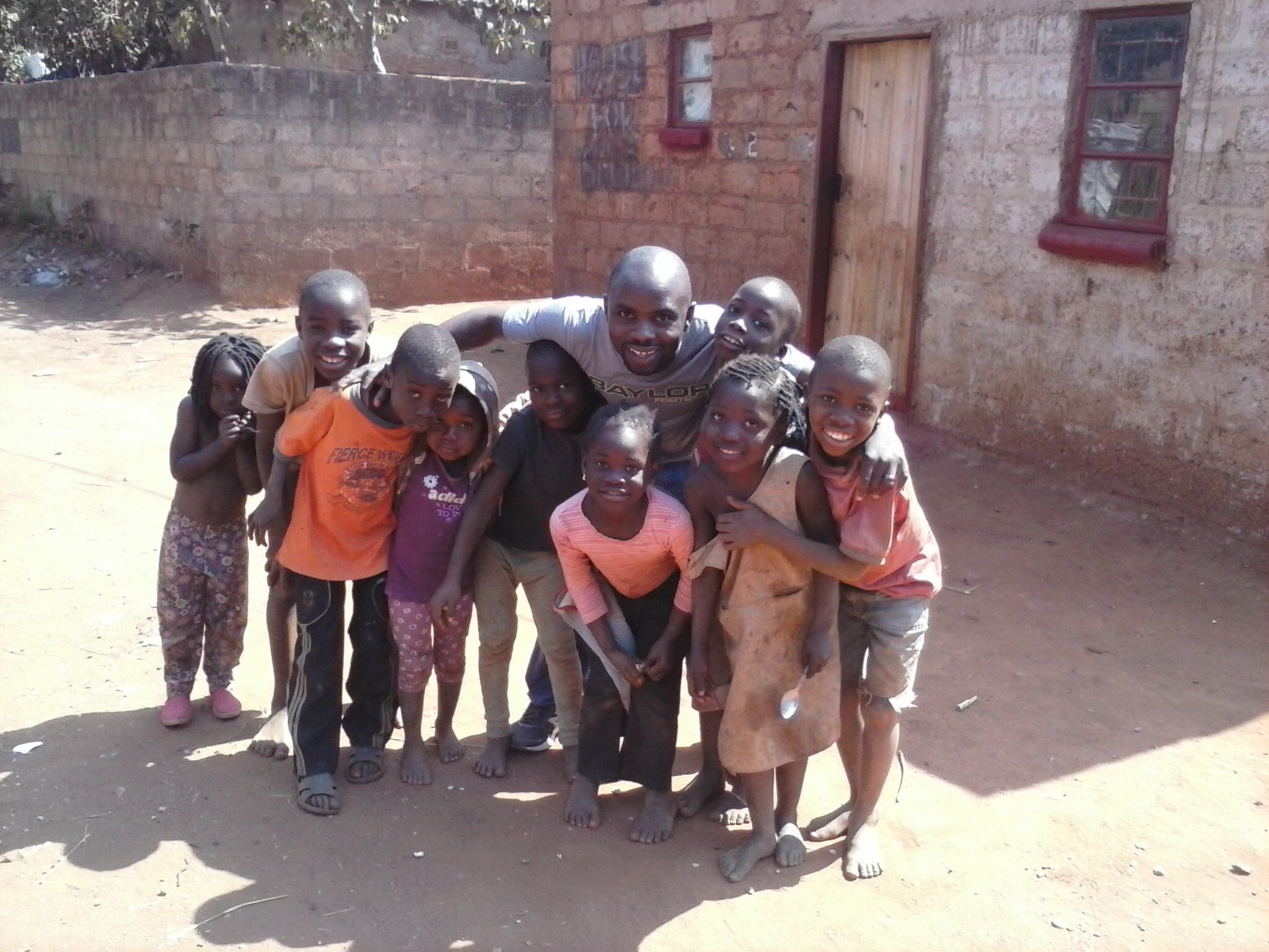 Mulenga and the children in Chainda compound share a big group hug, August 2014.