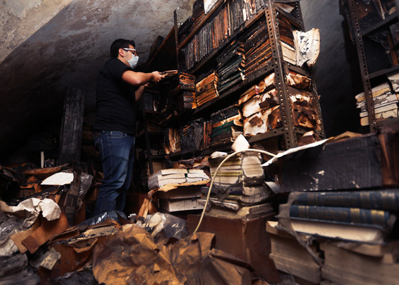 Charred books in Tripoli's Al-Saeh library. (Courtesy Hussein Malla/AP)