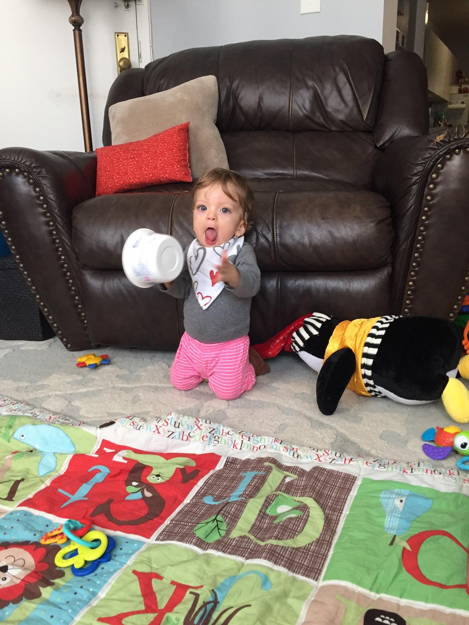 "Singing while she ""plays"" the yogurt bucket."