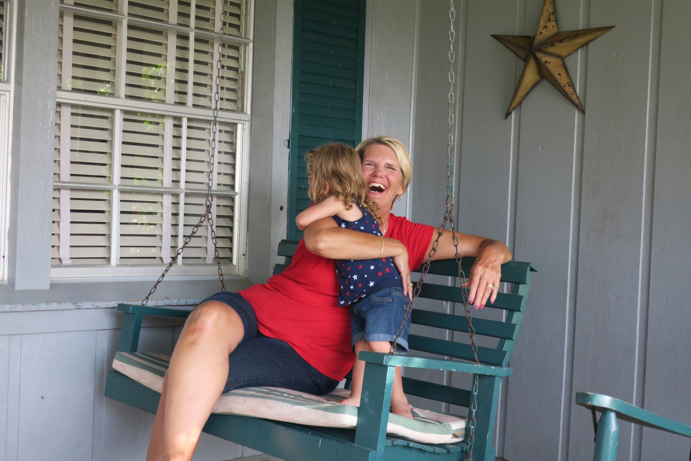 "Playing on the porch swing with Grandma. Lucie would hold the chain and sing, ""the wind is beHIND me!"" from the Moana's song,  How Far I'll Go ."
