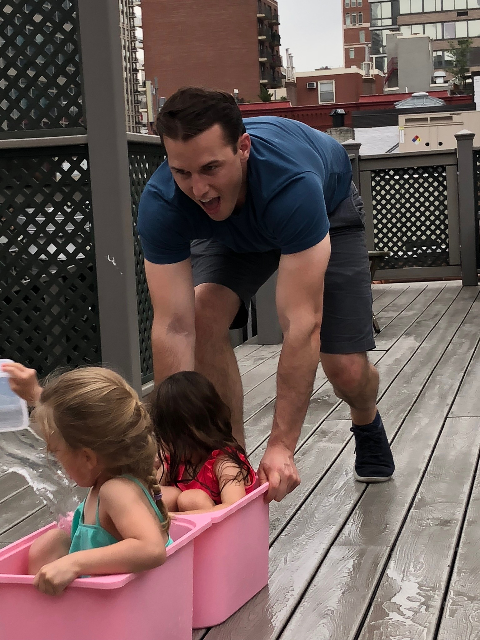 Uncle Greg pushing the girls in the buckets