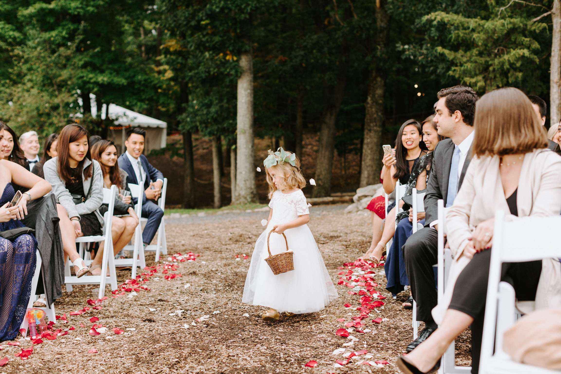 When Lucie got to the top of the aisle we watched as her face shifted from excitement to embarrassment. She got nervous from all the attention and although she didn't cry, she didn't smile either. This is a great shot from the photographer of Lucie begrudgingly throwing the petals over her shoulder.