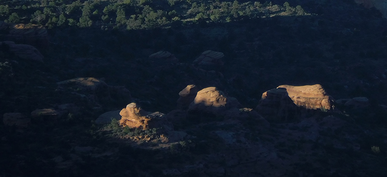 Early morning light striking the peaks of formations on a plateau far below us