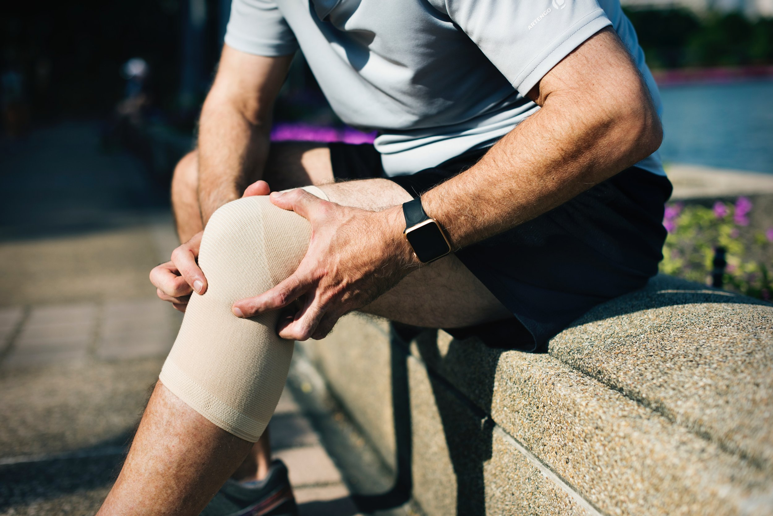Young man in pain with a bandage around his knee who needs rehabilitation from an injury in Yaletown, Vancouver