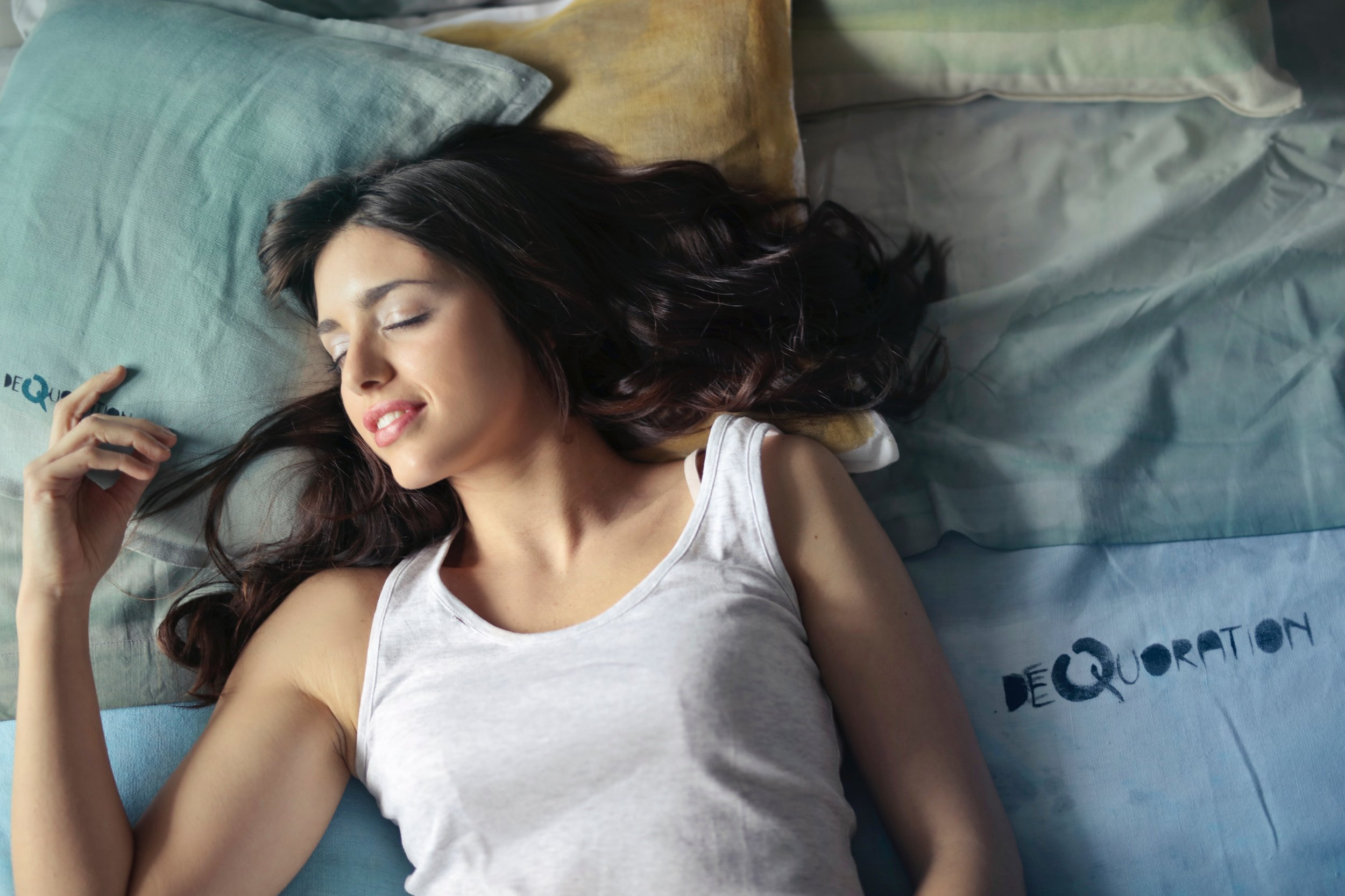 attractive white women sleeping with white tank top smiling in bed long black hair
