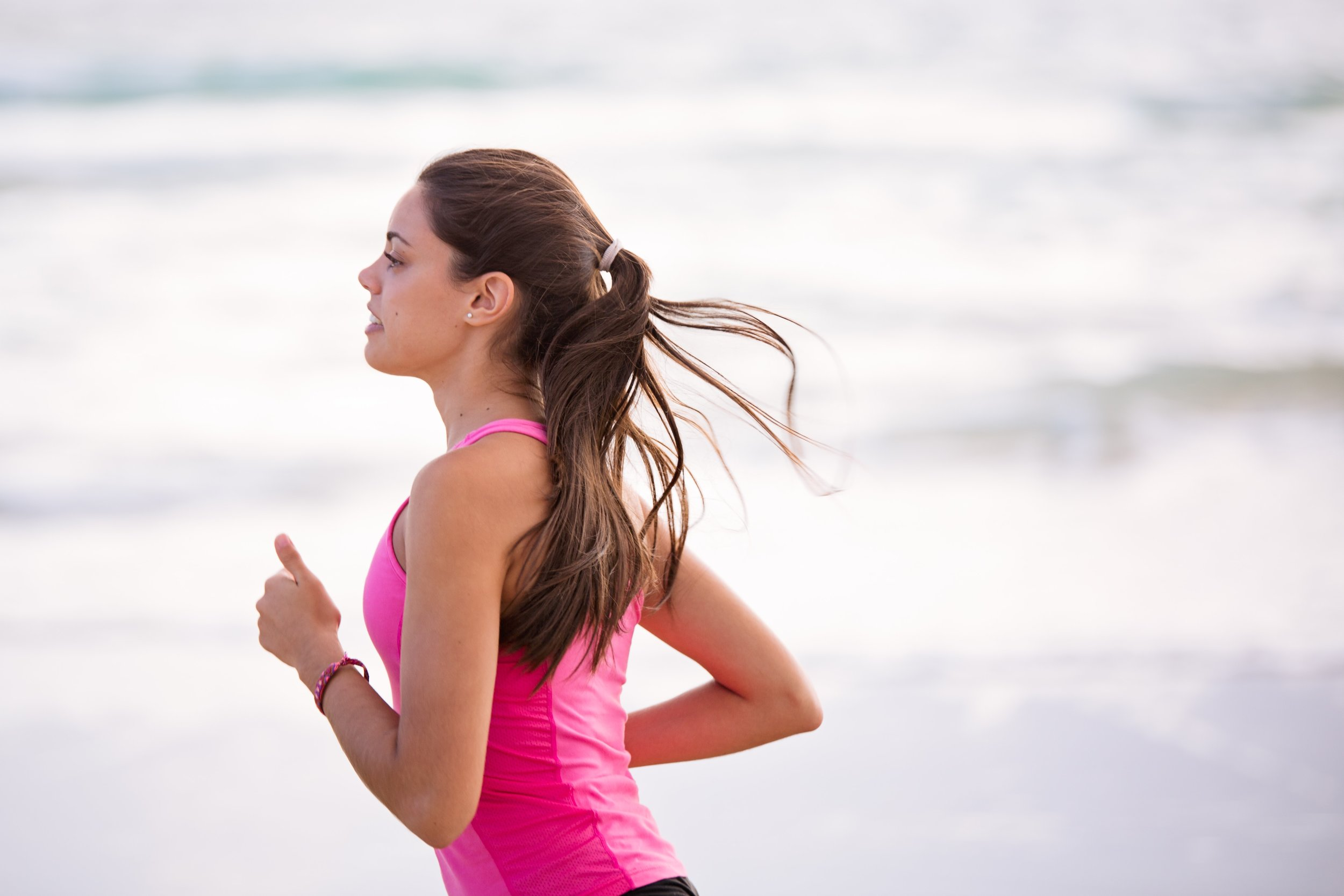 fitness jog white women with long black hair running next to beach wearing pink top