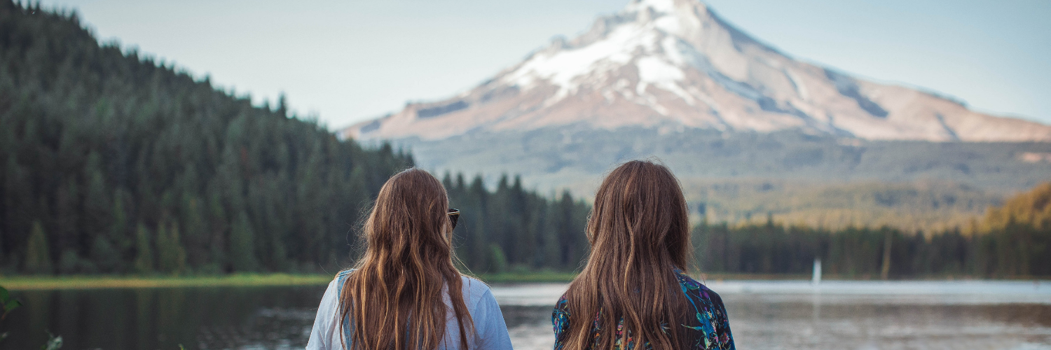two women with long brown hair on vacation and looking at a mountain