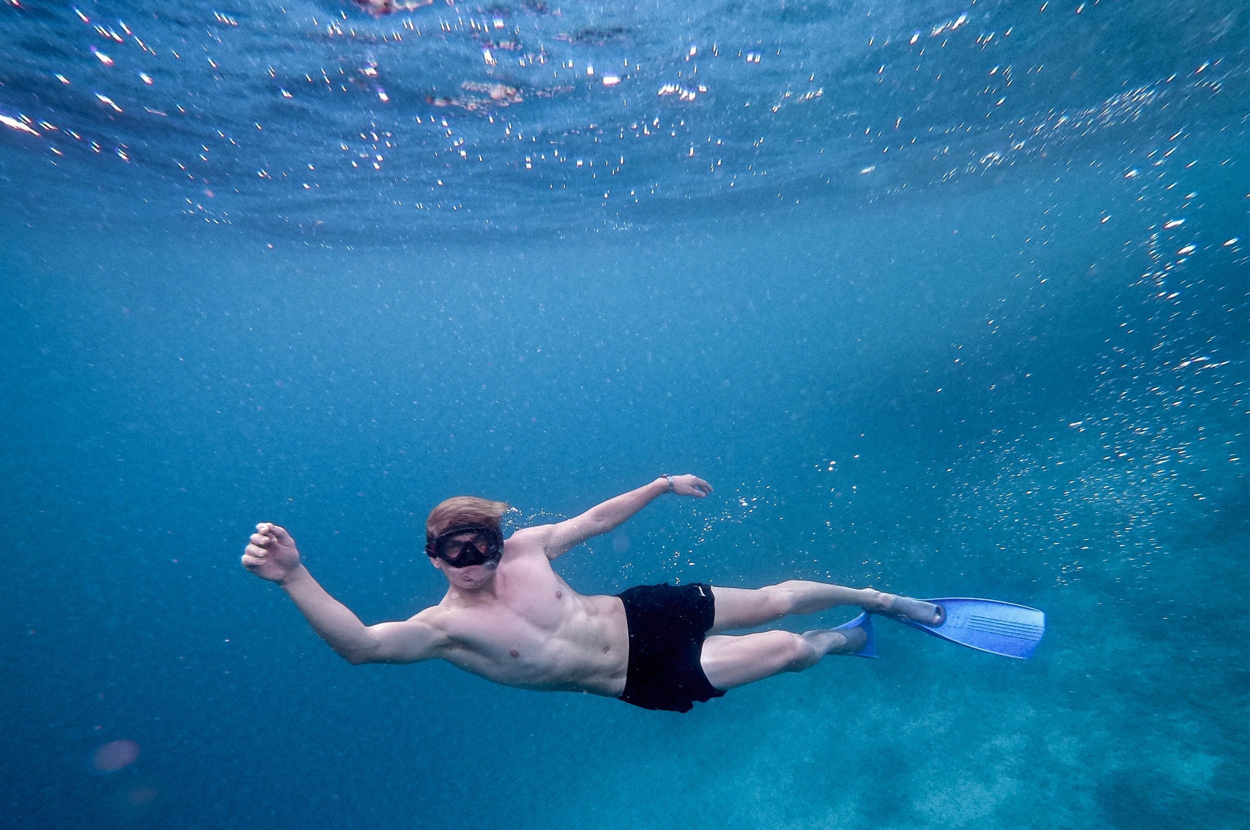 man swimming underwater in blue calm water topless with flippers