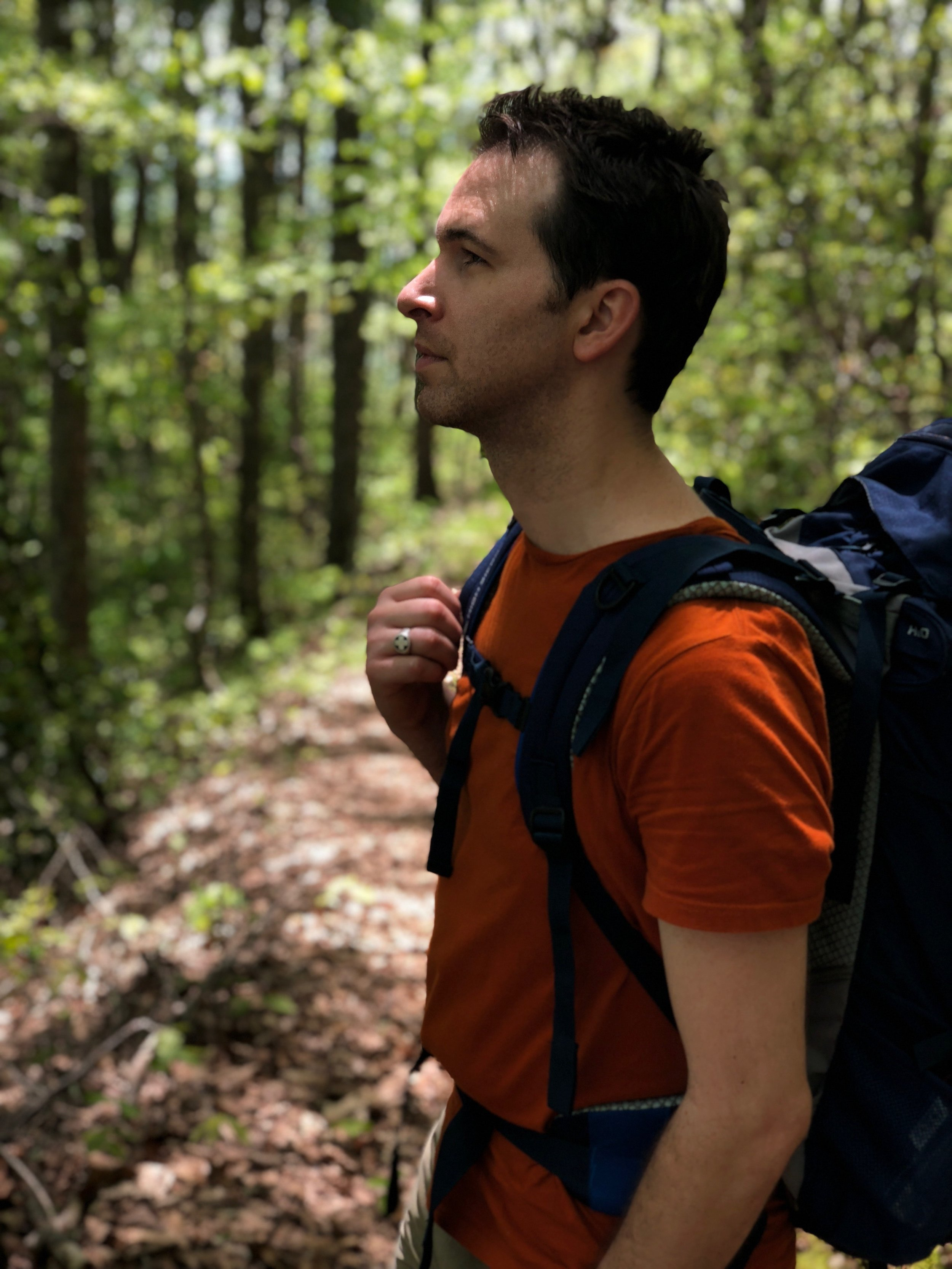 a white man with brown hair in forest looking up and hiking