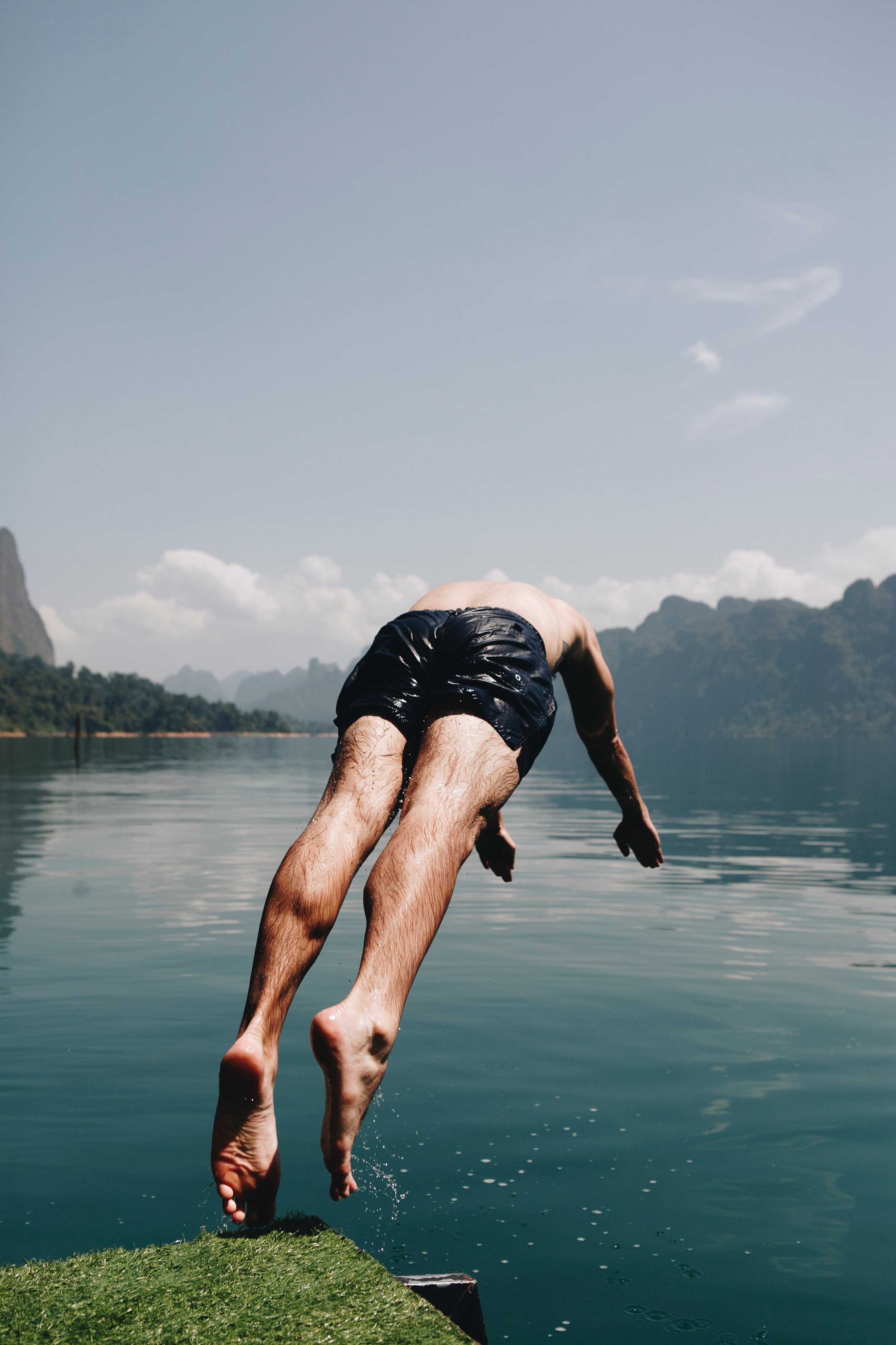 man in swim trunks diving into quiet lake water in Vancouver