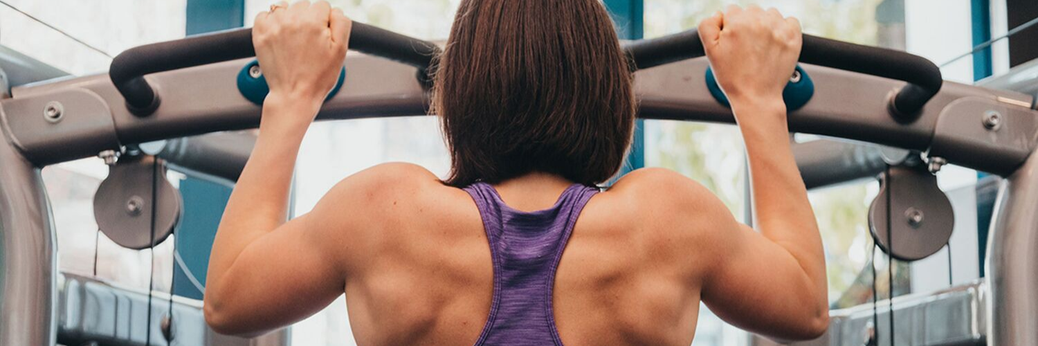 Kinesiologist woman doing pull ups in a gym in purple tank top