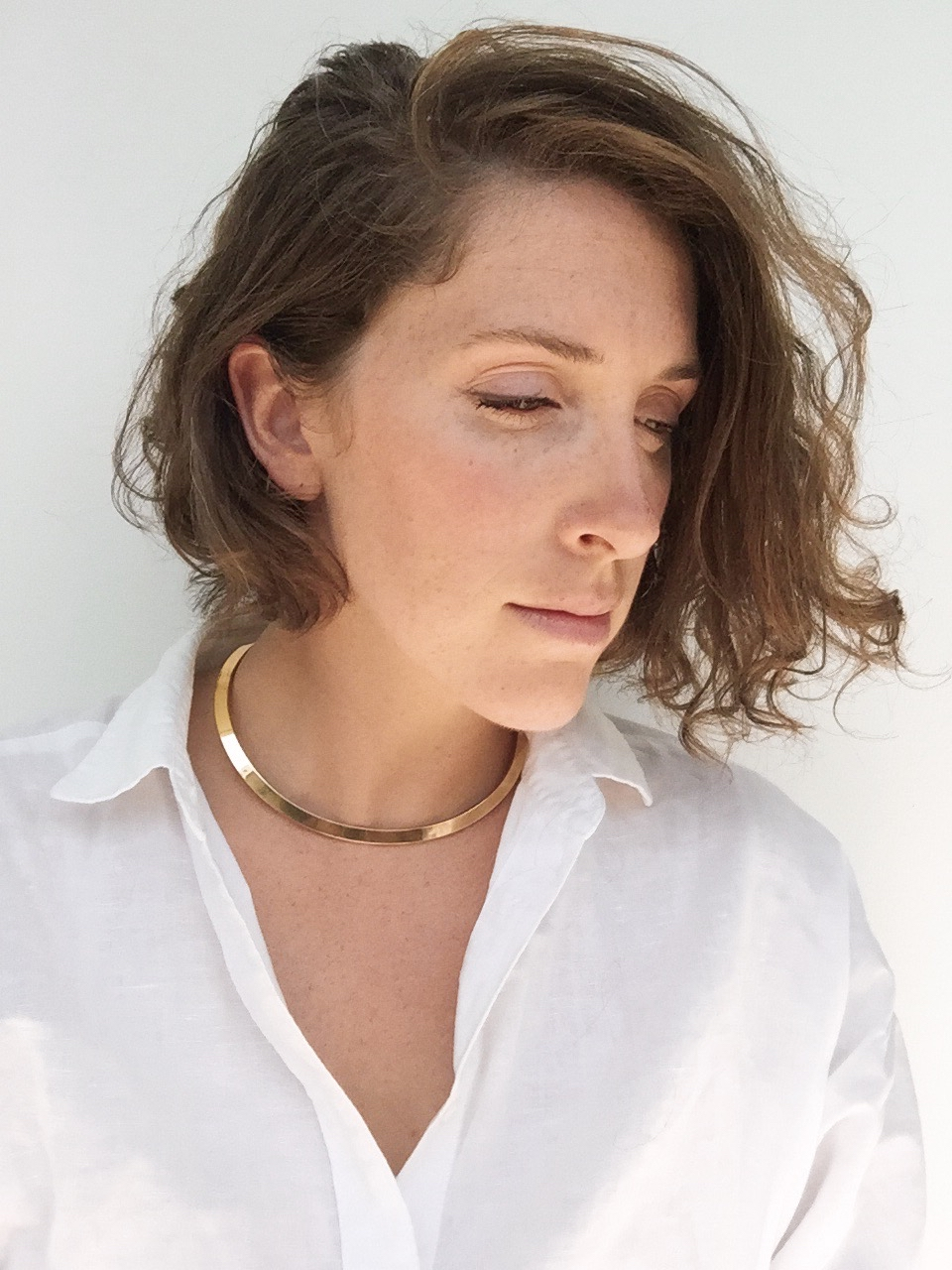 Curly haired woman in white linen and minimalist gold choker