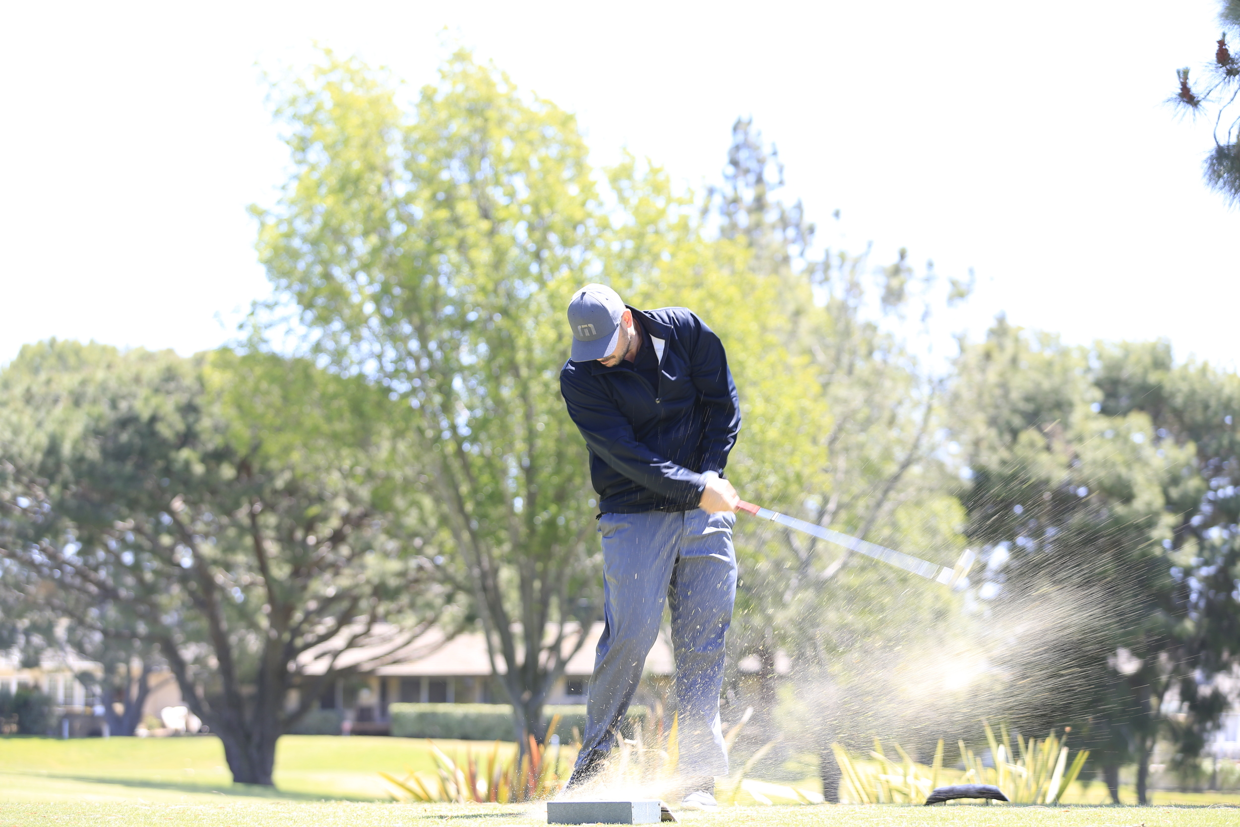 Golfer smacking a ball down range.