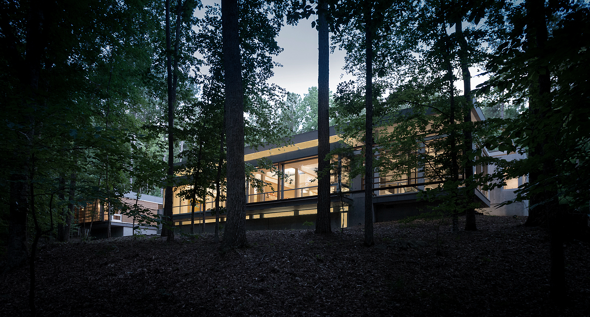 Bugg House   Durham, North Carolina   Architect:  HA    Program:   A 4,500sf (450m2) private residence is located in a heavily wooded, eight acre sight facing a stream to the north. The house is organized as a series of 4 pavilions: living/dining, master bedroom, guest bedrooms (2), and a garage/storage. The pavilions are connected by glass enclosed corridors. The services spaces are expressed as cast in place concrete volumes.   Client:   Withheld