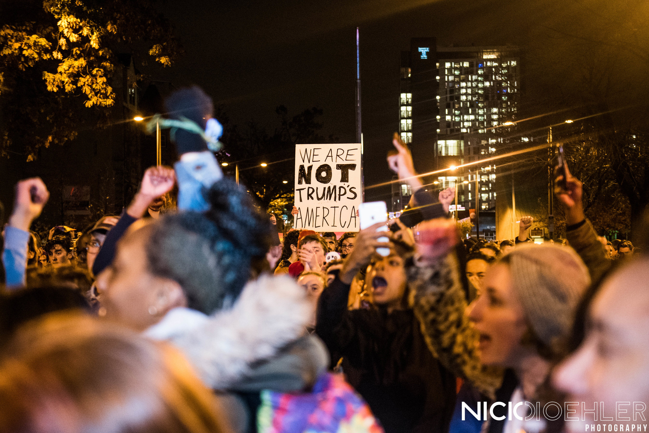 """A sign (""""We Are Not Trump's America"""")amidst all the people protesting."""