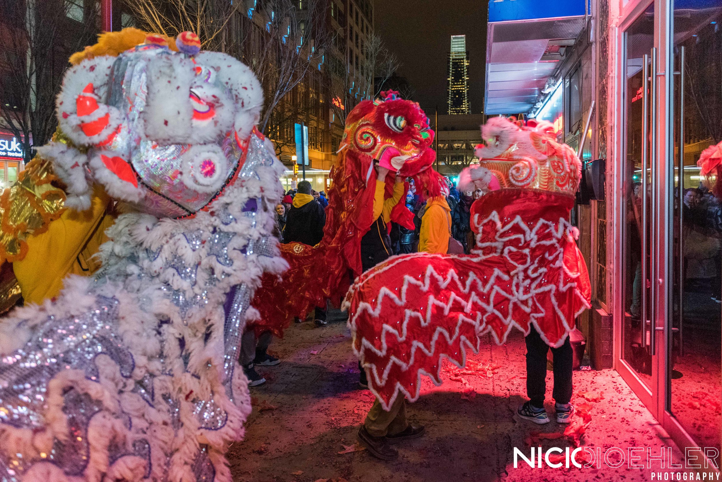 Lion Dancers dancing in front with Center City in the background.