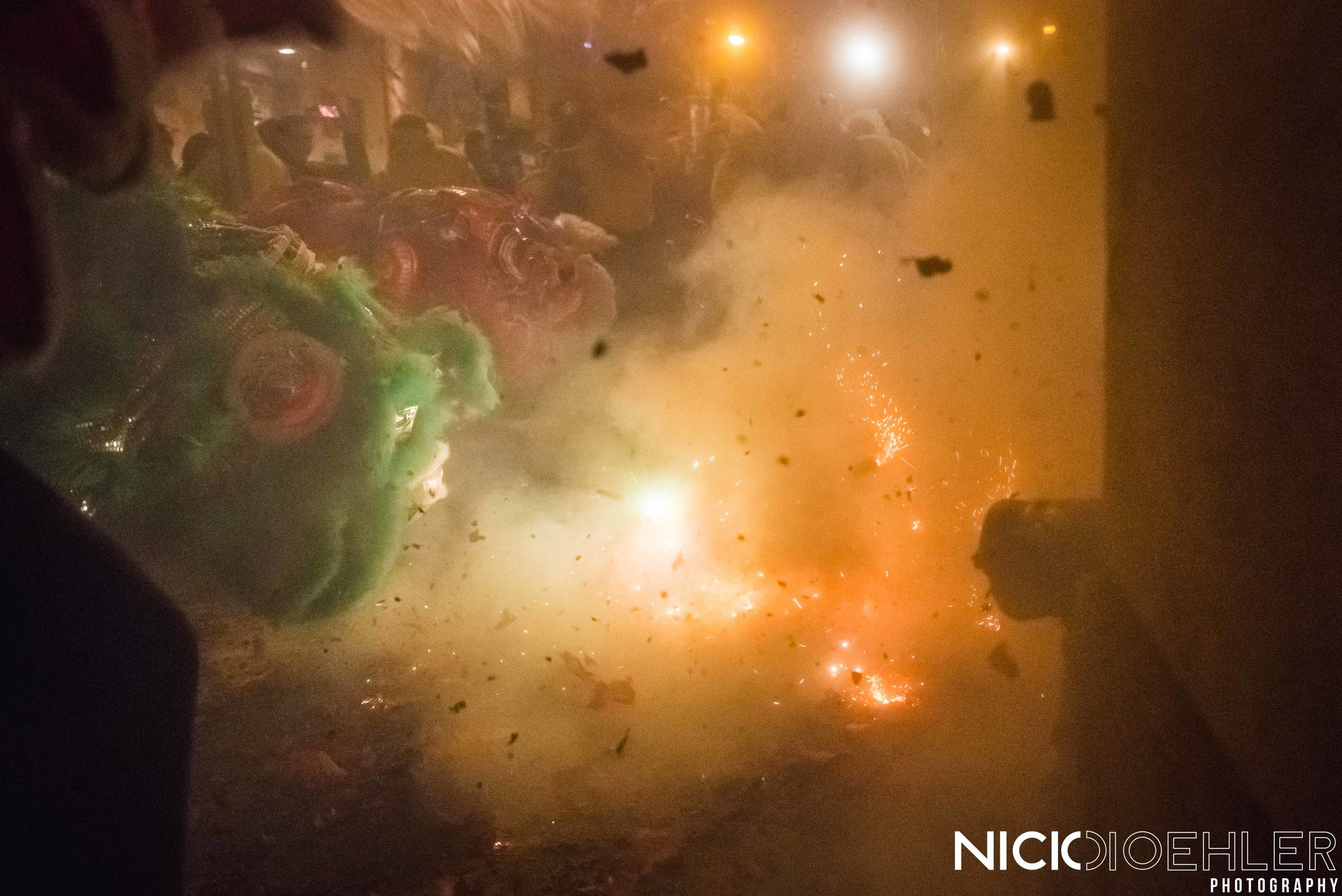 Firecrackers igniting in front of the Lion Dancers.