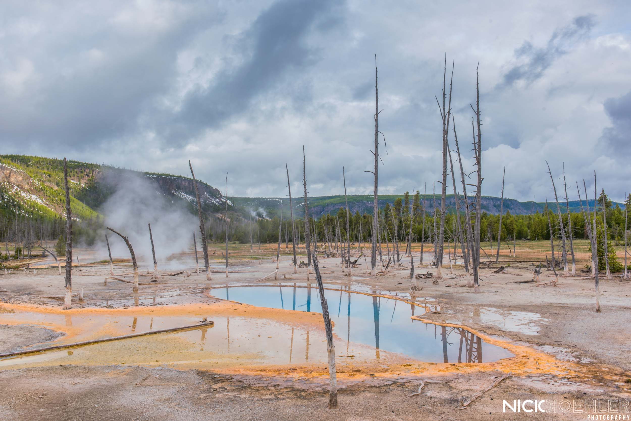 Yellowstone National Park: A geyser steams as a beautiful blue hot spring gives great color.