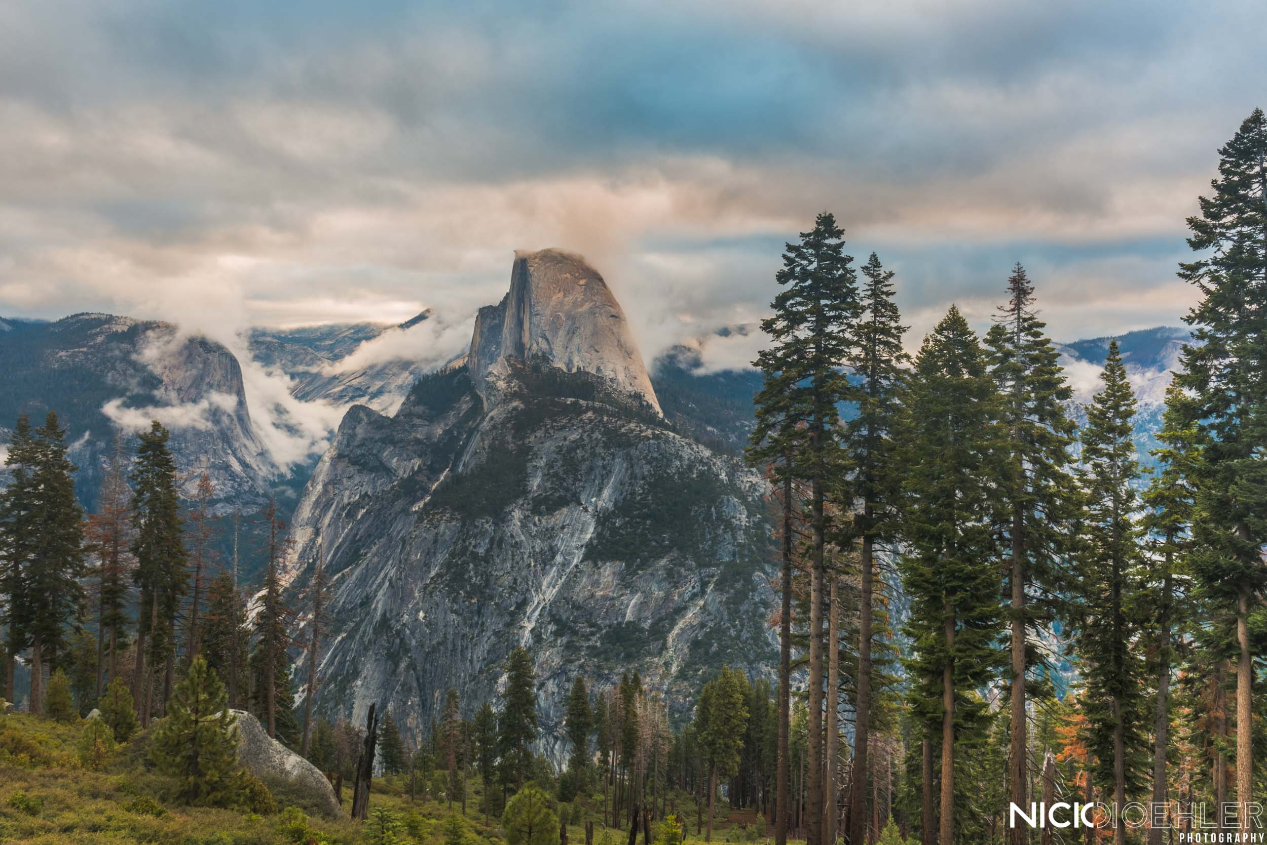 Yosemite National Park: Half Dome controlling clouds as a beautiful red sunrise leaks in.