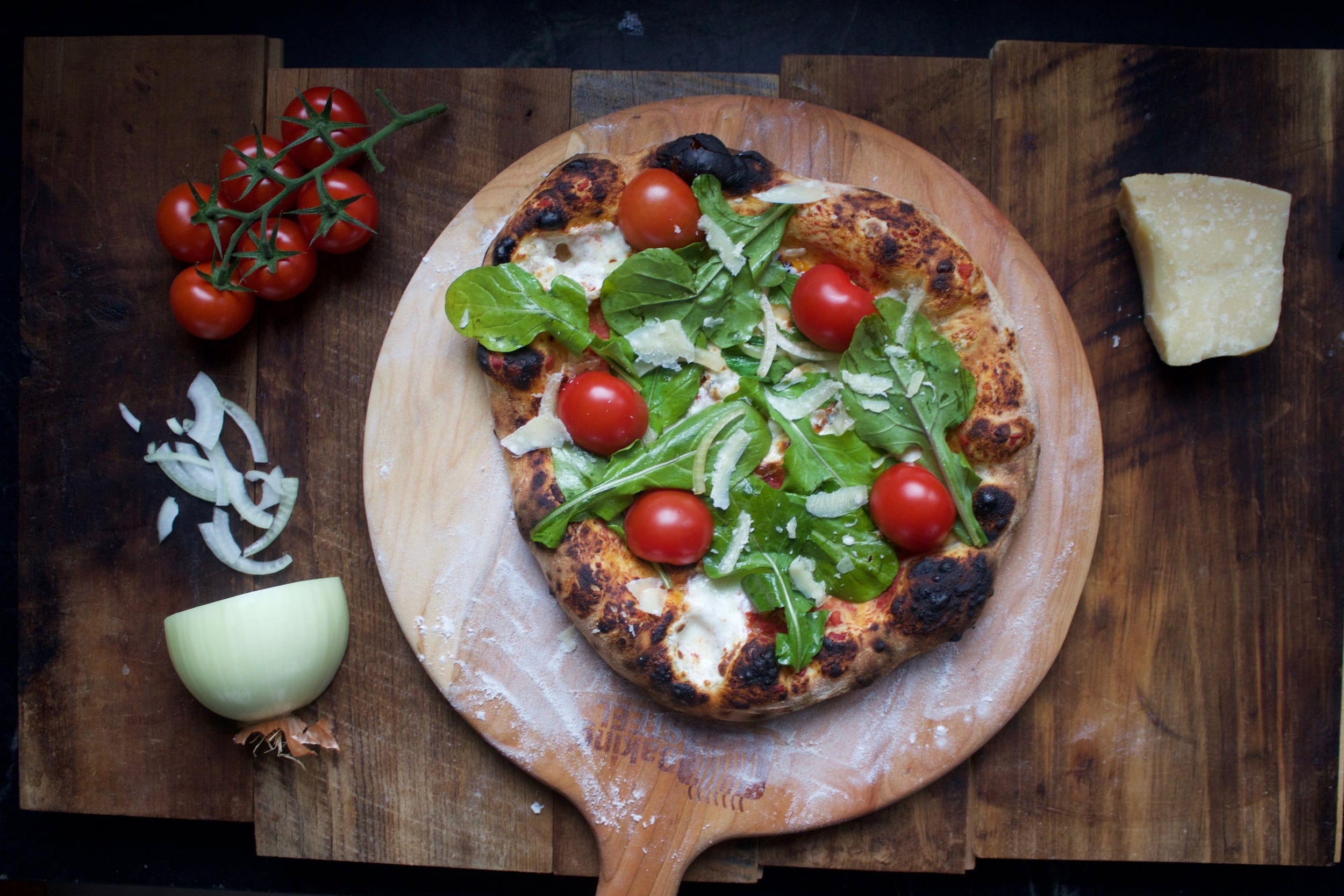 arugula and tomato pizza on a Baking Steel