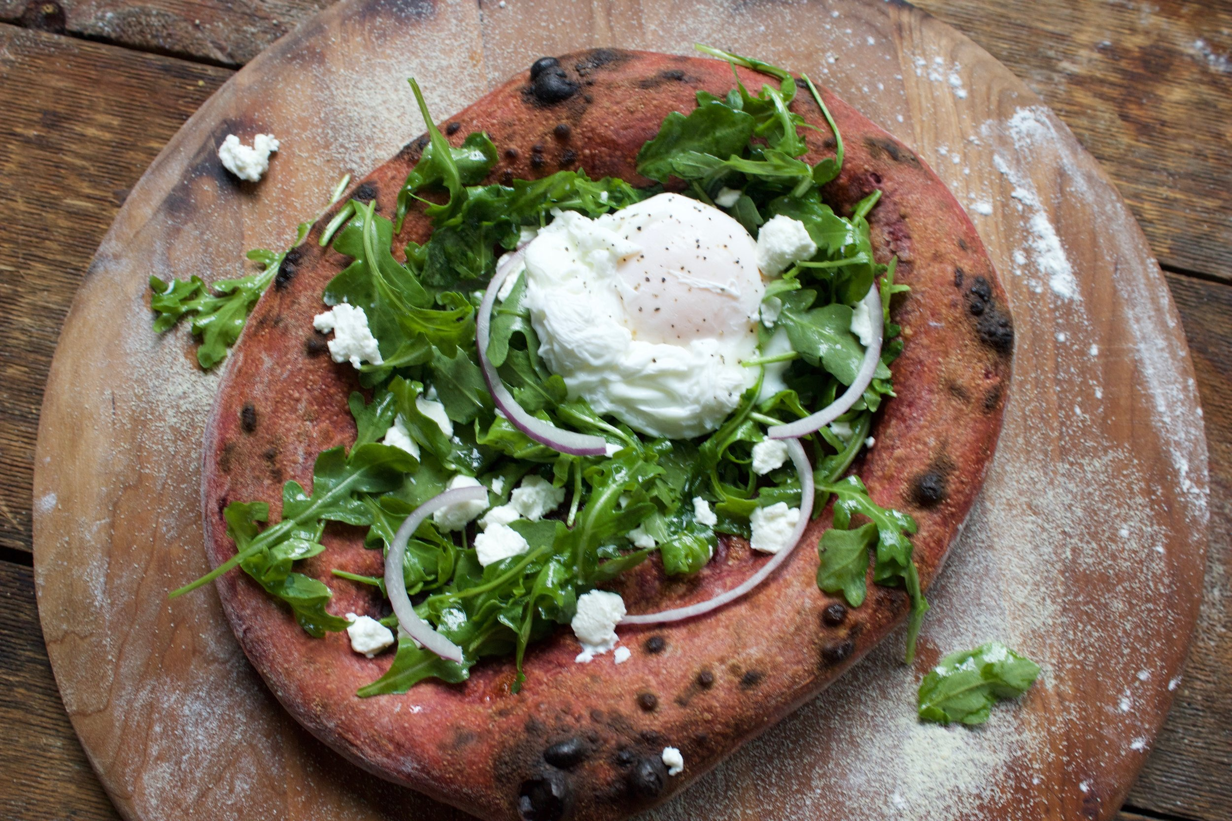 beet and arugula pizza with a poached egg