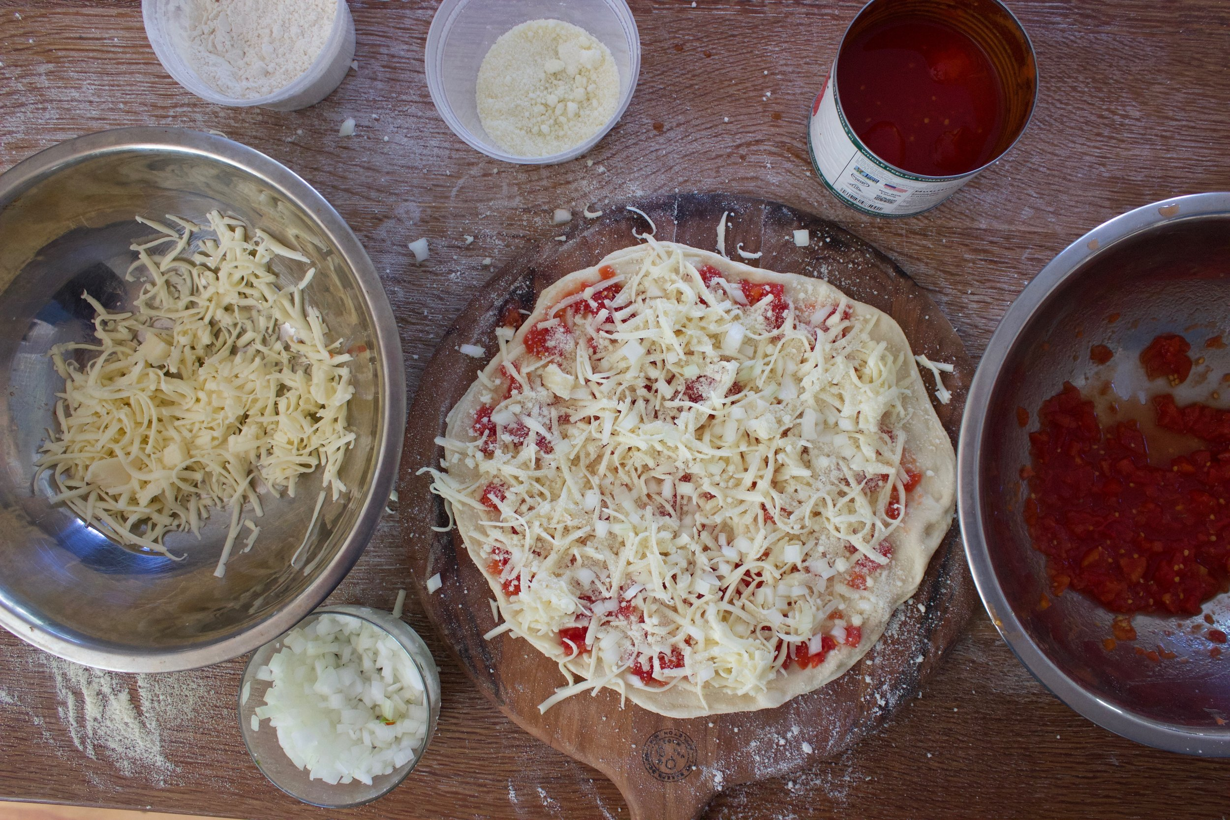 The dough stretched out beautifully. We topped this one with tomato sauce, shredded fontina and chopped white onion.