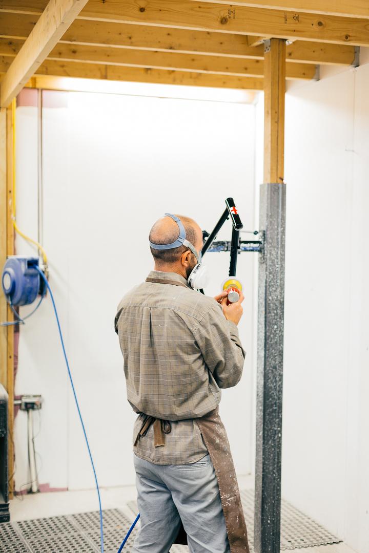 Noah Rosen sands the frames and parts between coats of paint.