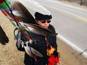 Sharon Day carrying the eagle feather staff and copper pail of water. Photo credit Kevin E. Schmidt.