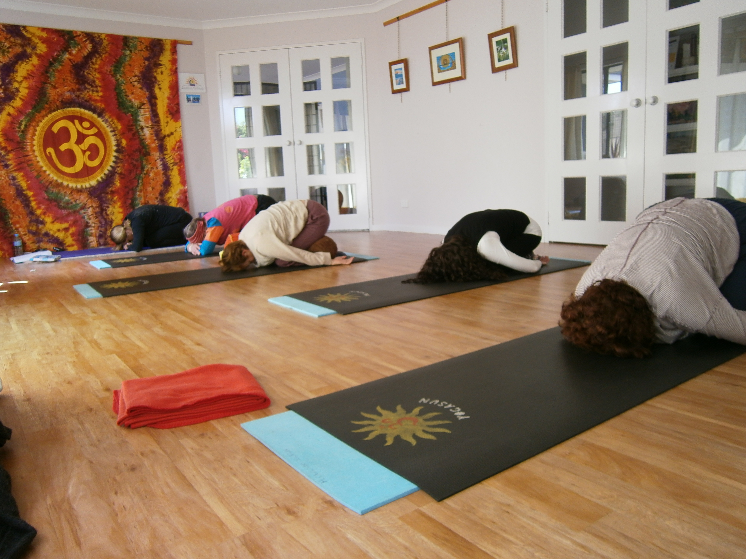 Students resting in Child Pose during a yoga class.