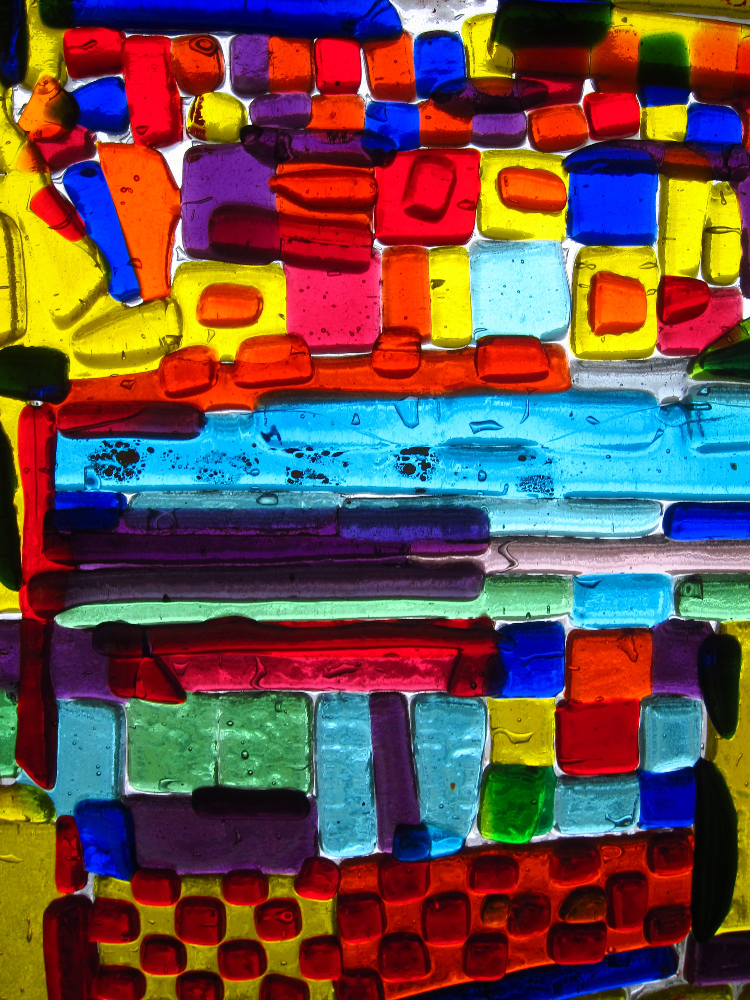 Detail of one of my fused glass works.   Private collection,  Cambridge, MA.  Basically, I was fooling with colors, knowing that it will look different after the work is fired.   I did not anticipate the effect of the empty spaces between colors and how they will look.   Click on the image to expand it.