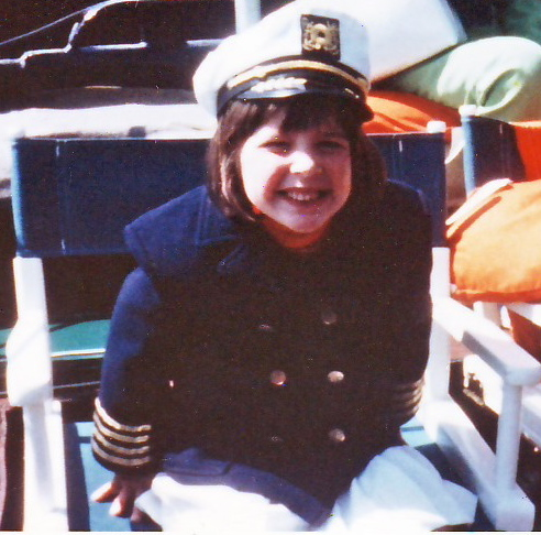 """Here's me with my captain's hat and jacket on the tugboat my Great Grandfather named after me when I was 6. He said """"Remember, you're the captain of your own ship!"""" Marvelous advice."""