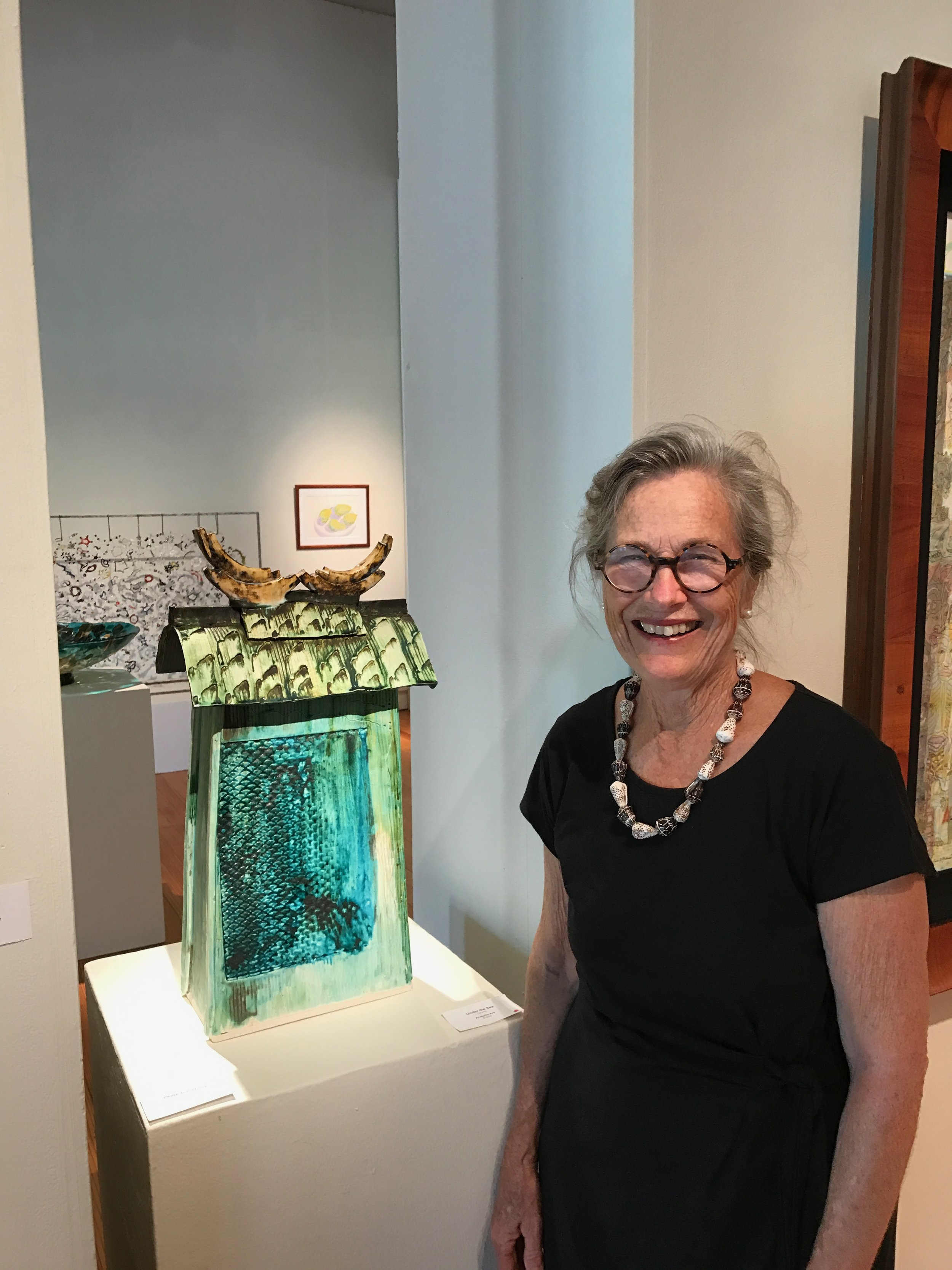 Maui Crafts Guild member AraBella Ark at the opening of the new ArtMAUI 2107next to her entry that was accepted and sold.
