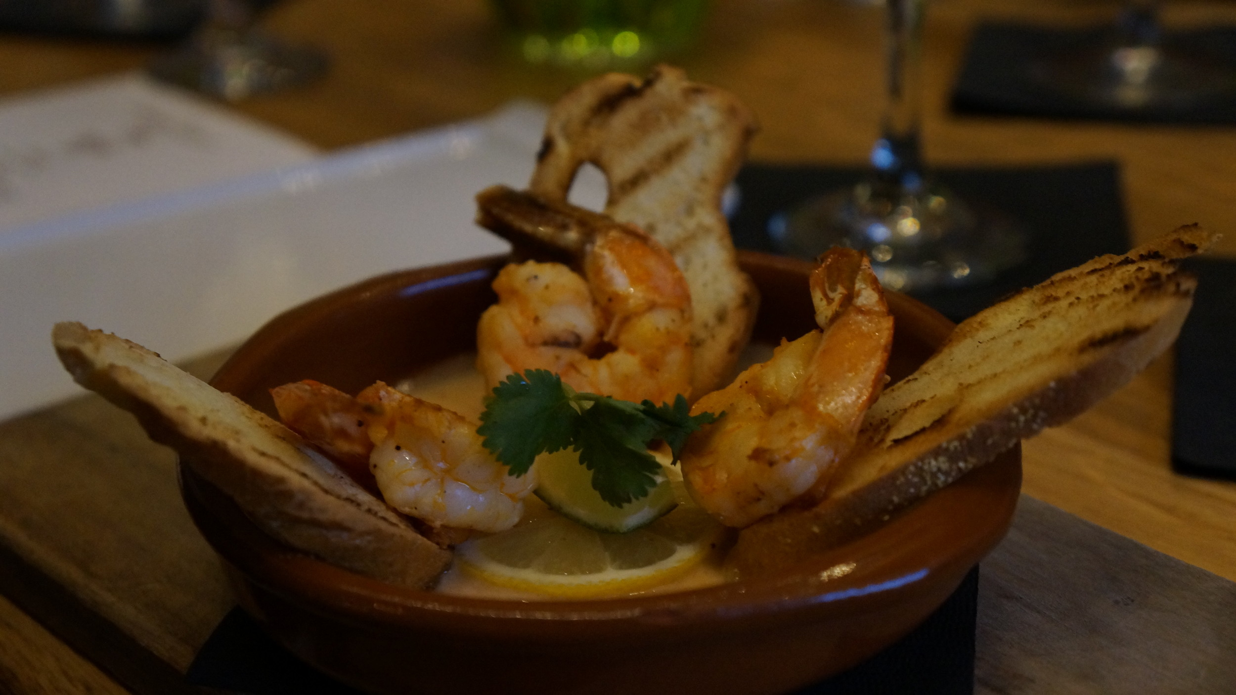 Shrimp a la Plancha :   La Plancha is a reference to a griddle or a grill that we use to cook the shrimp. This simple shrimp dish is elevated to new heights by using Kasa's house made coconut red curry sauce with lime and butter.