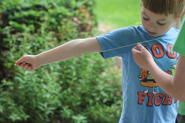 Use household string to measure one arm length and cut. Measure another for the entire wingspan. With the long string in hand, thread on a metal washer. Tie strings to eyehooks on dowel rods, and you're ready to roll!