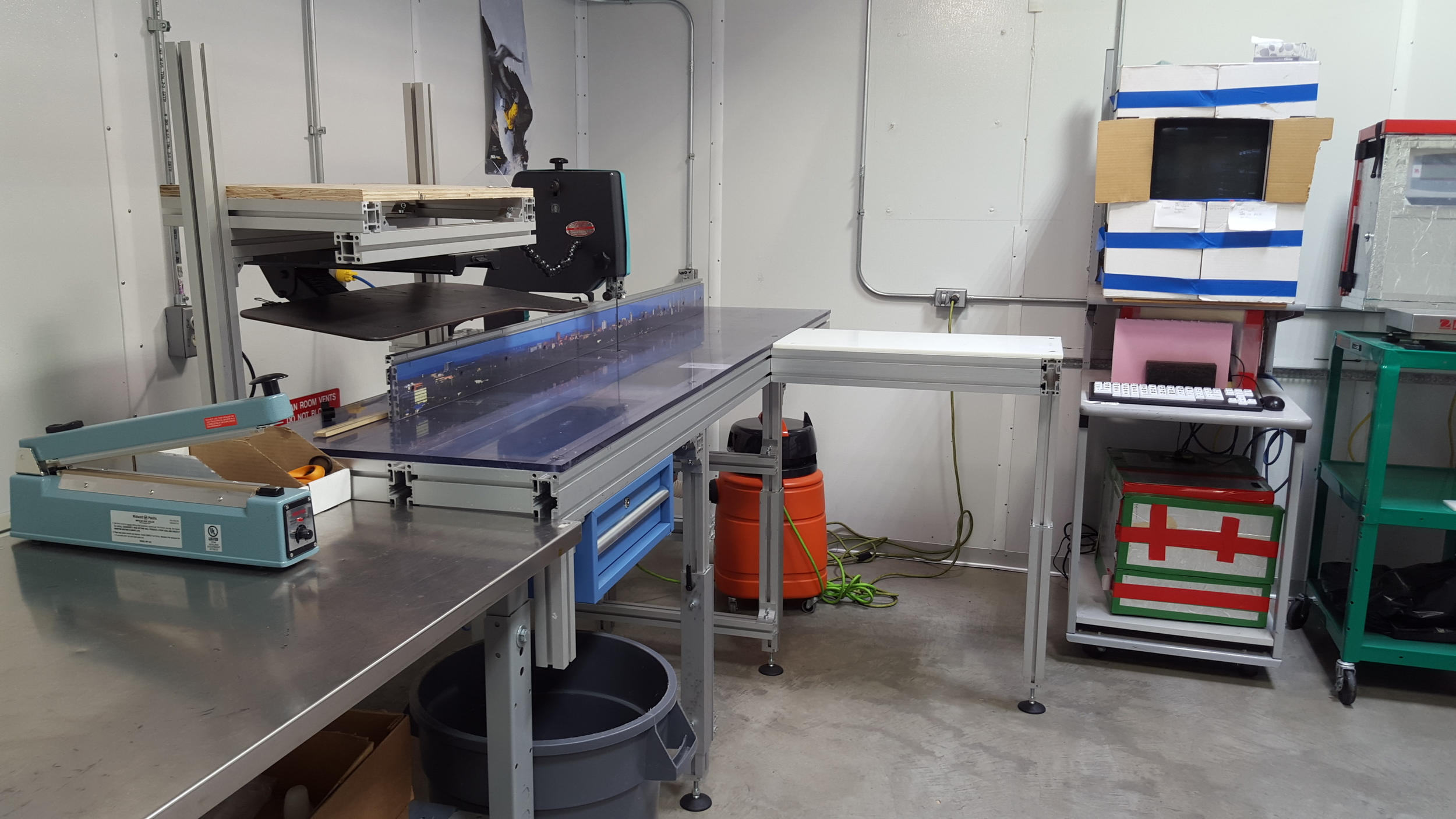 """Our ice-cutting station in the """"warm"""" room. Those cardboard boxes on the right are makeshift insulation for the computer, which otherwise wouldn't work at these temperatures."""
