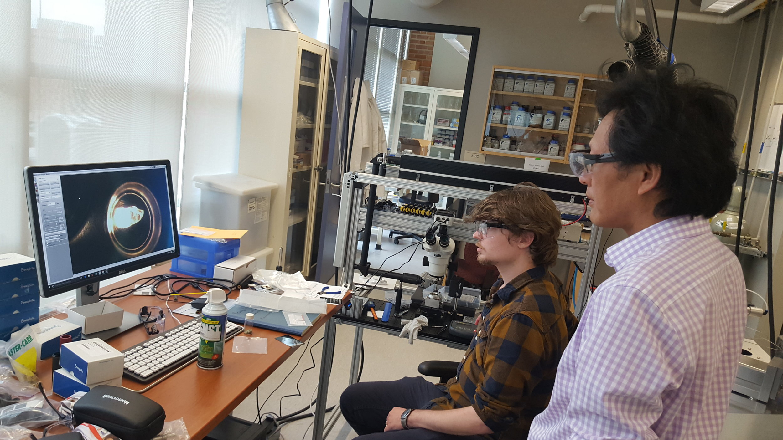Justin operating the laser-fluorination line (Cin-Ty looking on) to extract oxygen from minerals for isotopic analysis. Justin uses the oxygen to learn about ancient environments.