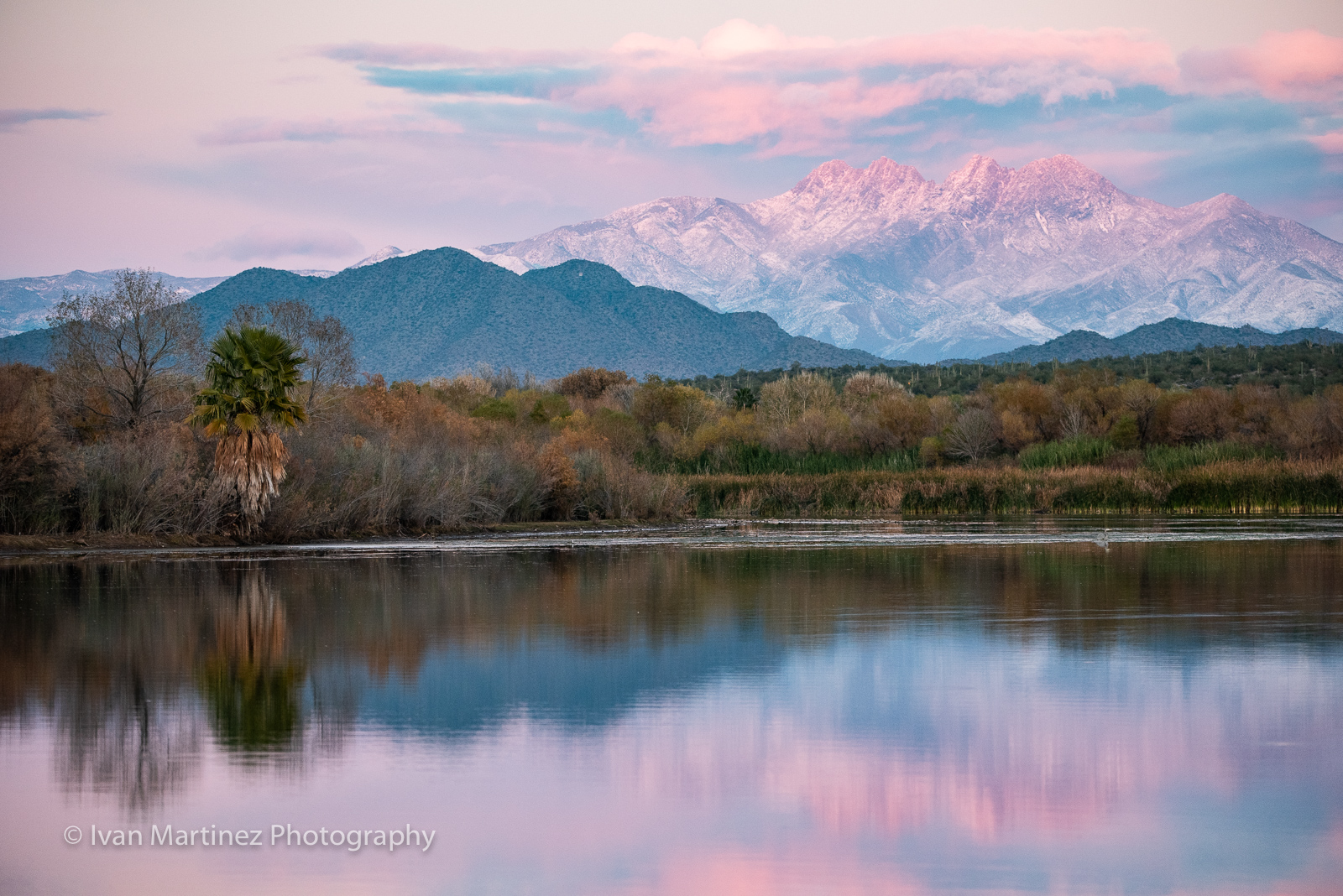 A reflection of snow covered Four Peaks at sunset time