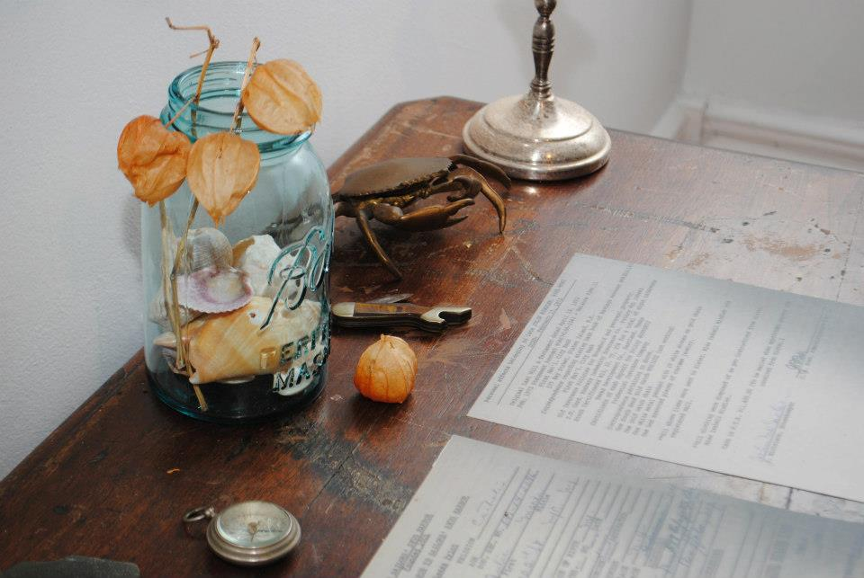 a desk with a document, blue jar with sea shells, crab-shaped ash tray, compass, and pocket knife