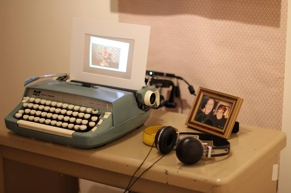 video is rear projected onto paper in a blue typewriter on a desk with headphones, ash tray, and framed picture of two older women