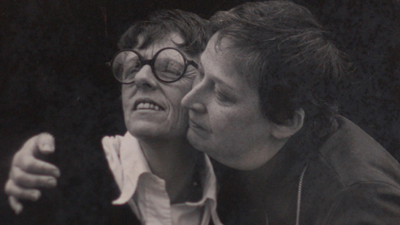 a black and white photo of two women embracing