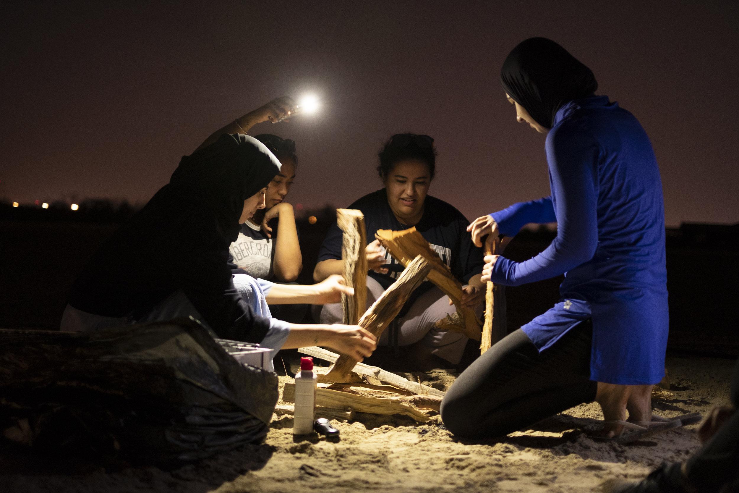 4 young women making the camp fire_Abu Dhabi_(c)Oliver Wheeldon.jpg