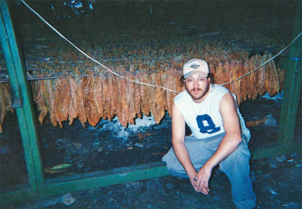 Jonathan shows off tobacco in a curing barn.