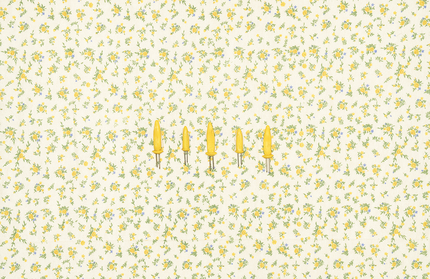 Corn Cob Holders on Tablecloth with Yellow Flowers